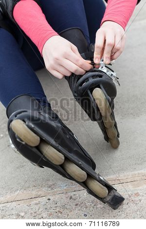 Girl Putting On Her Rollerblades