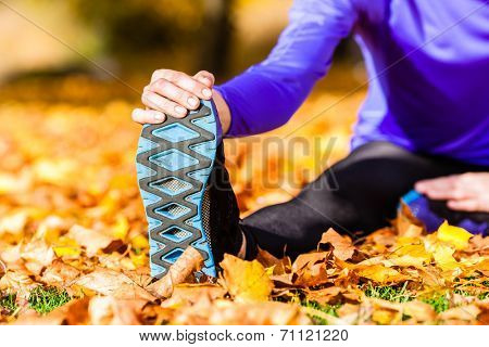 Sportswoman sport stretching in autumn leaves