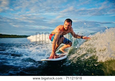 Sporty man surfboarding in the sea