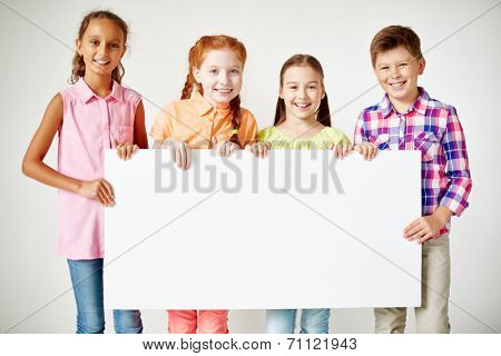 Friendly classmates with blank paper looking at camera with smiles