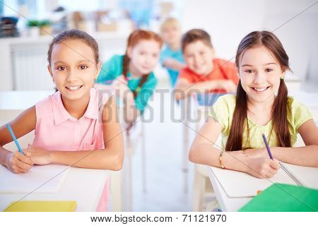 Two adolescent girls sitting at drawing lesson