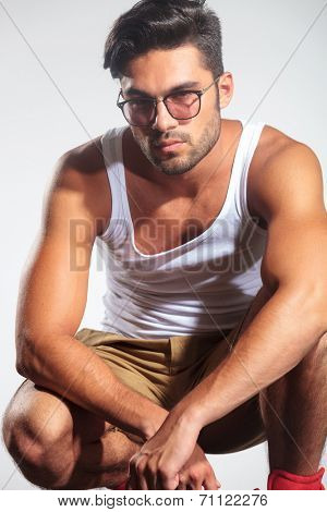 serious casual man in undershirt standing crouched in studio