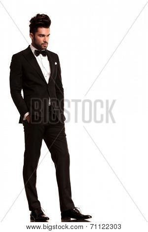 fashion man in tuxedo looking to his side, full body picture on white background