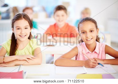 Two adolescent girls looking at camera at lesson