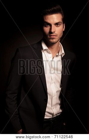 young relaxed business man with hands in his pockets on dark background