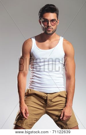 portrait of a fit man in undershirt and glasses on grey studio background