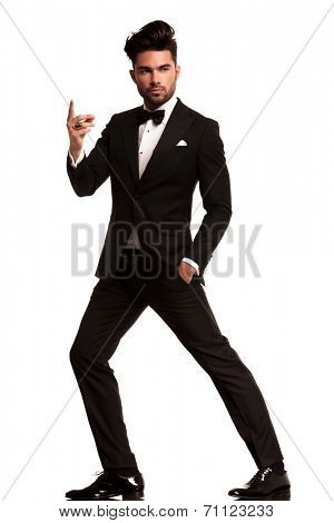 fashion man in tuxedo snapping his finger , full body picture on white background