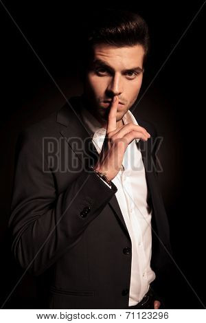 elegant fashion man making the quiet sign with finger over his mouth on black background