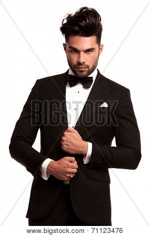 stylish man in elegant black suit and bowtie looking at the camera on white background
