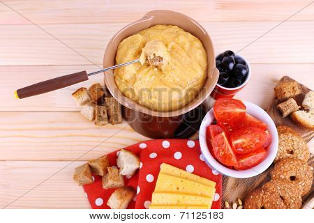 Fondue, tomatoes, biscuits, slices of cheese and rusks on cutting board on polka dot napkin on wooden background