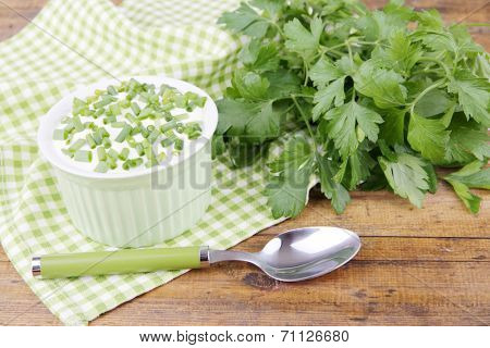 Plastic round bowl of cream with a tuft of parsley near it on a napkin on wooden background