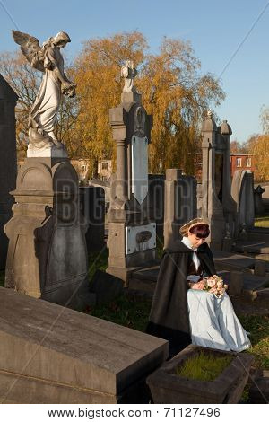 Ancient graveyard and a Victorian widow holding roses