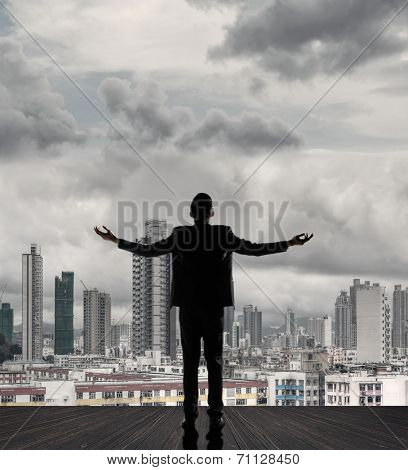 Silhouette of businessman open arms against city with copyspace.
