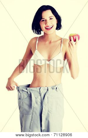 Young woman showing how much weight did she lost. Isolated on white