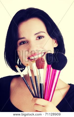 Young make-up artist woman holding brushes , isolated on white
