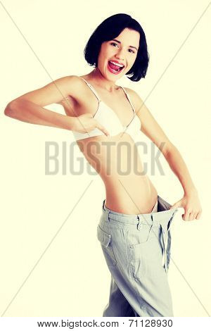 Young fit woman showing how much weight did she lost. Isolated on white