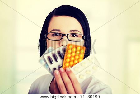Portrait of beautiful doctor or nurse holding prescription drugs isolated over white background