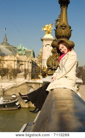 Happy Beautiful Woman Sitting On The Balustrade Of The Pont Alexandre Iii In Paris