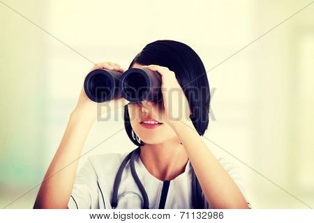 Atractive medical girl looking through binoculars isolated on white background