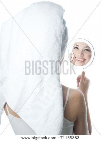 closeup portrait of attractive  caucasian smiling woman brunette isolated on white studio shot lips toothy smile face  head and shoulders looking at mirrow cleaning face cotton disc