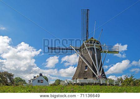 Windmill on a dike under a blue sky