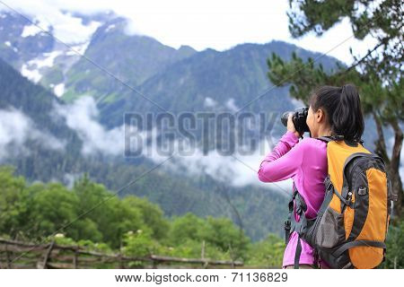woman photographer taking photo with cell phone at mountain peak in tibet,china