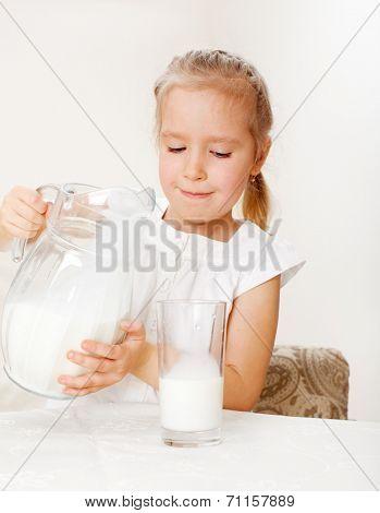 Child with glass pitcher milk. Little girl drinking milk for breakfast