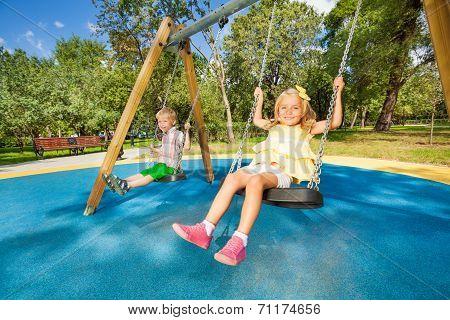 Two cute children swinging on playground