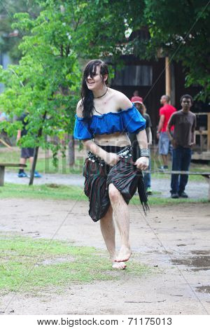 MUSKOGEE, OK - MAY 24: A girl dances in water and mud after rain at the Oklahoma 19th annual Renaissance Festival on May 24, 2014 at the Castle of Muskogee in Muskogee, OK.