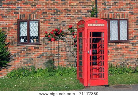 Nostalgic Phone Box In Front Of Red Brick Wall With Rambler Rose