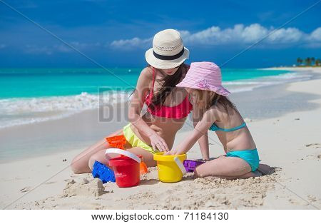 Little cute girl and mother building sandcastle at tropical beach