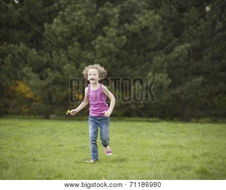 Young girl running through park in summer