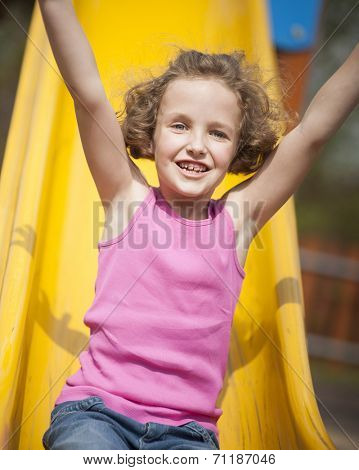 Close-up view of young girl on slide in playground