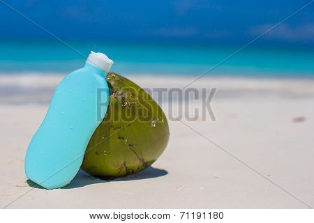 Coconut and suncream on white sand