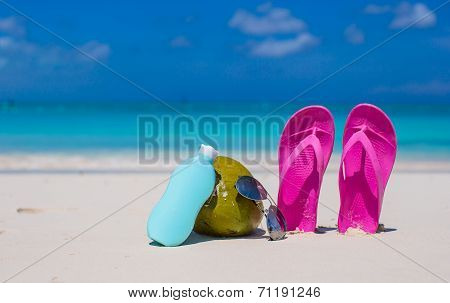 Flip flops, coconut and suncream on white sand