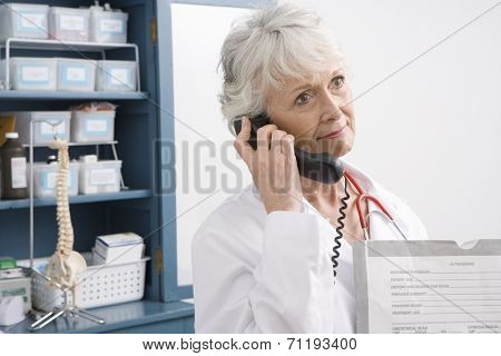 Senior medical practitioner stands on phone at medical cabinet