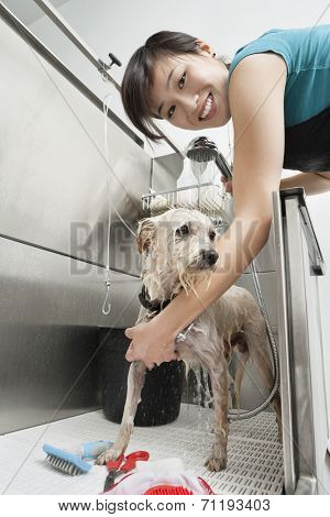 Portrait of young female animal groomer spraying water on dog