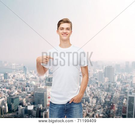 gesture, advertising and people concept - smiling young man in blank white t-shirt pointing finger on himself over city background