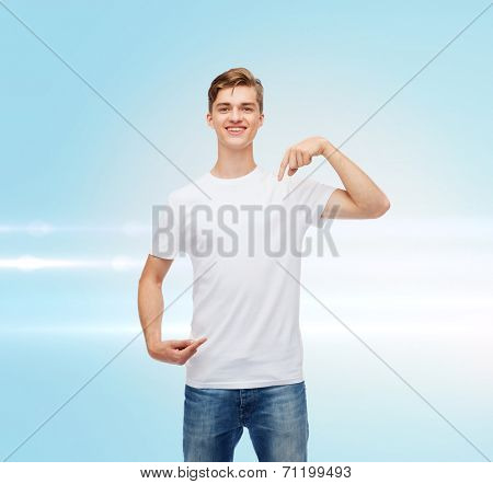gesture, advertising and people concept - smiling young man in blank white t-shirt pointing fingers on himself over blue laser background