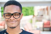 stock photo of nerd glasses  - Closeup headshot portrait of fine young man with big glasses undergrad student smiling isolated on outside outdoors background - JPG