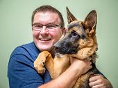 picture of alsatian  - Happy young man posing with its German shepherd pet - JPG