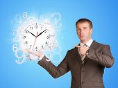 stock photo of time flies  - Businessman hold clock with flying figures - JPG