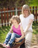 stock photo of seesaw  - Mother and daughter ride seesaw together - JPG