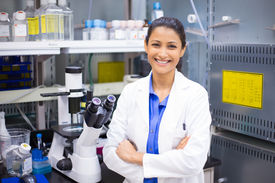 stock photo of histology  - Closeup portrait young smiling scientist in white lab coat standing by microscope - JPG