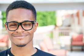 image of nerd glasses  - Closeup headshot portrait of fine young man with big glasses undergrad student smiling isolated on outside outdoors background - JPG