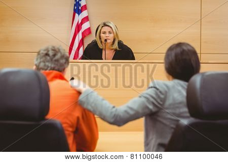 Judge and lawyer discussing the sentence for prisoner in the court room