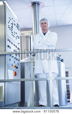 Smiling scientist standing with arms crossed in the factory