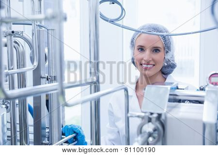 Portrait of a smiling scientist behind metal pipe in the factory