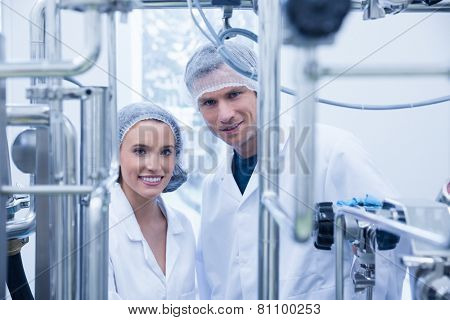 Scientist team behind metal gauge looking at camera in the factory