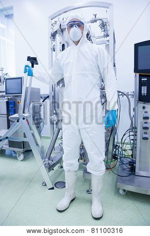 Scientist in protective suit holding ladder in the factory